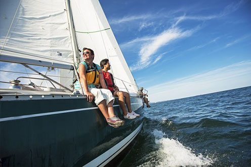 Sailors sit on the side of a sailboat as they enjoy a sunny day