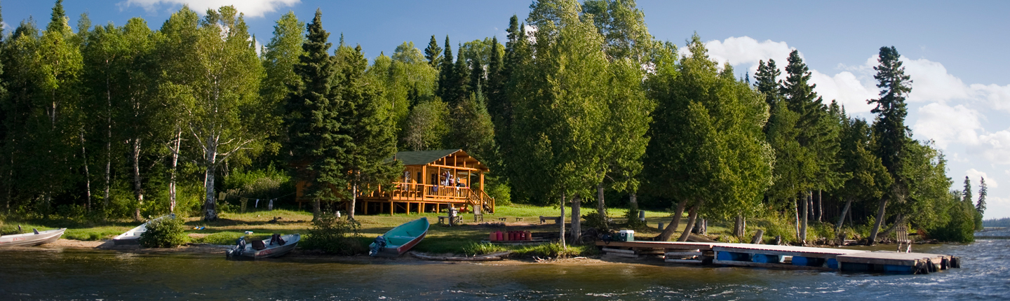 Waterfront view of boats, dock and a lodge surrounded by tall trees