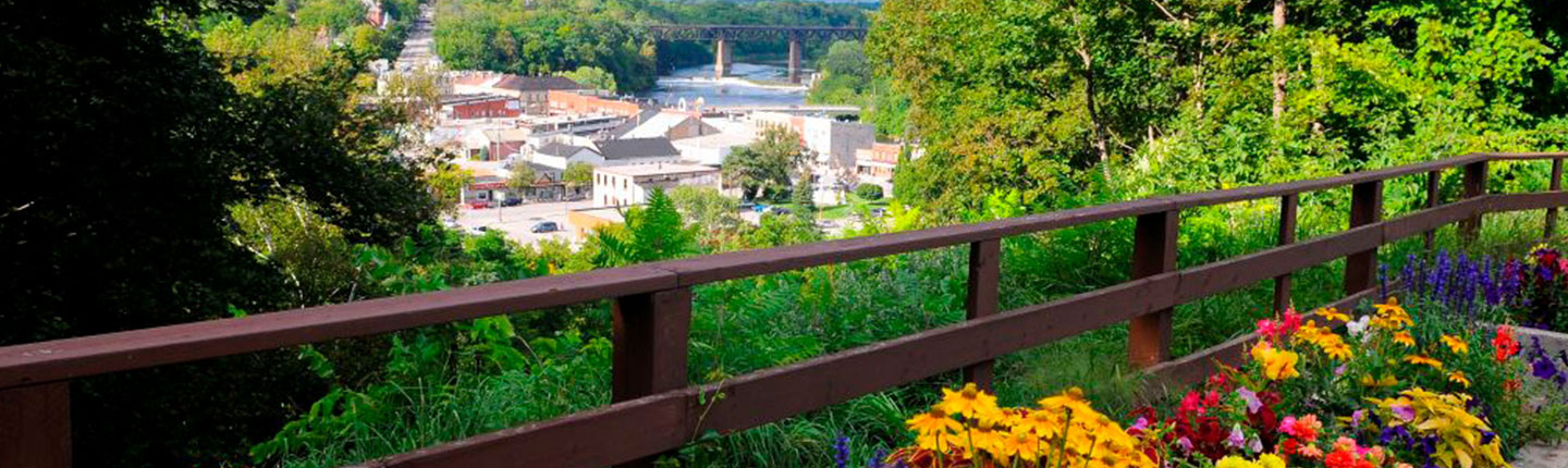 Planters with colourful flowers on a pedestrian bridge overlooking the town of Paris, Ontario and the Grand River