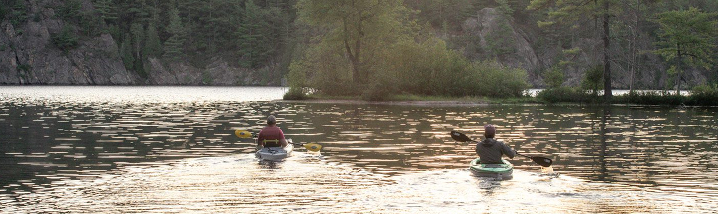 Two kayakers paddling on a calm waterway
