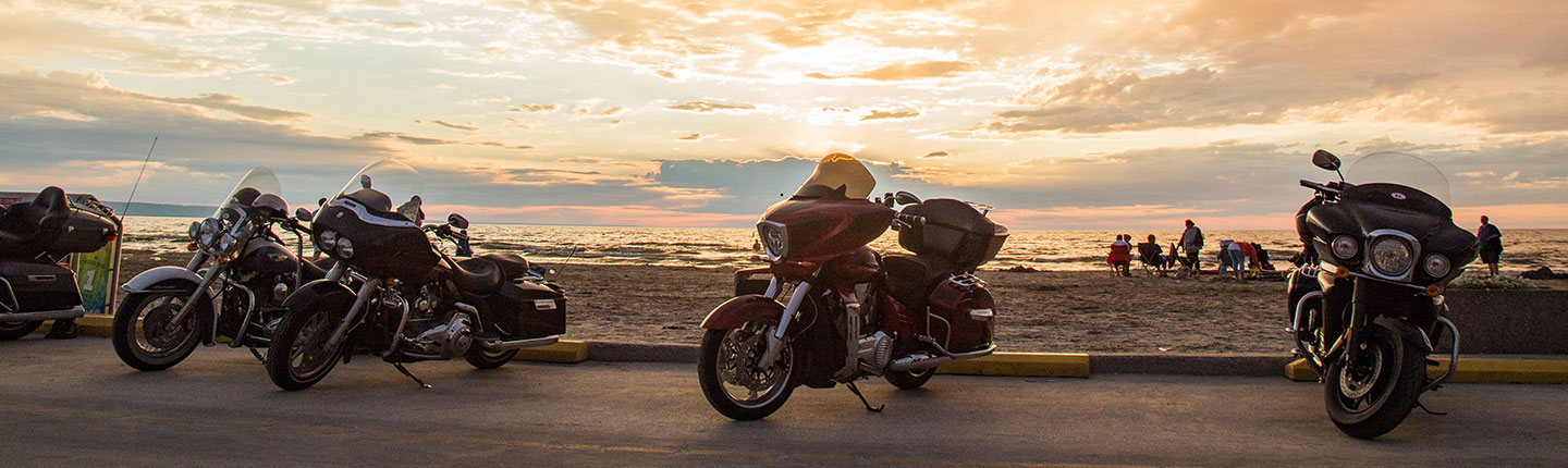 A row of motorcycles parked at a beach at sunset