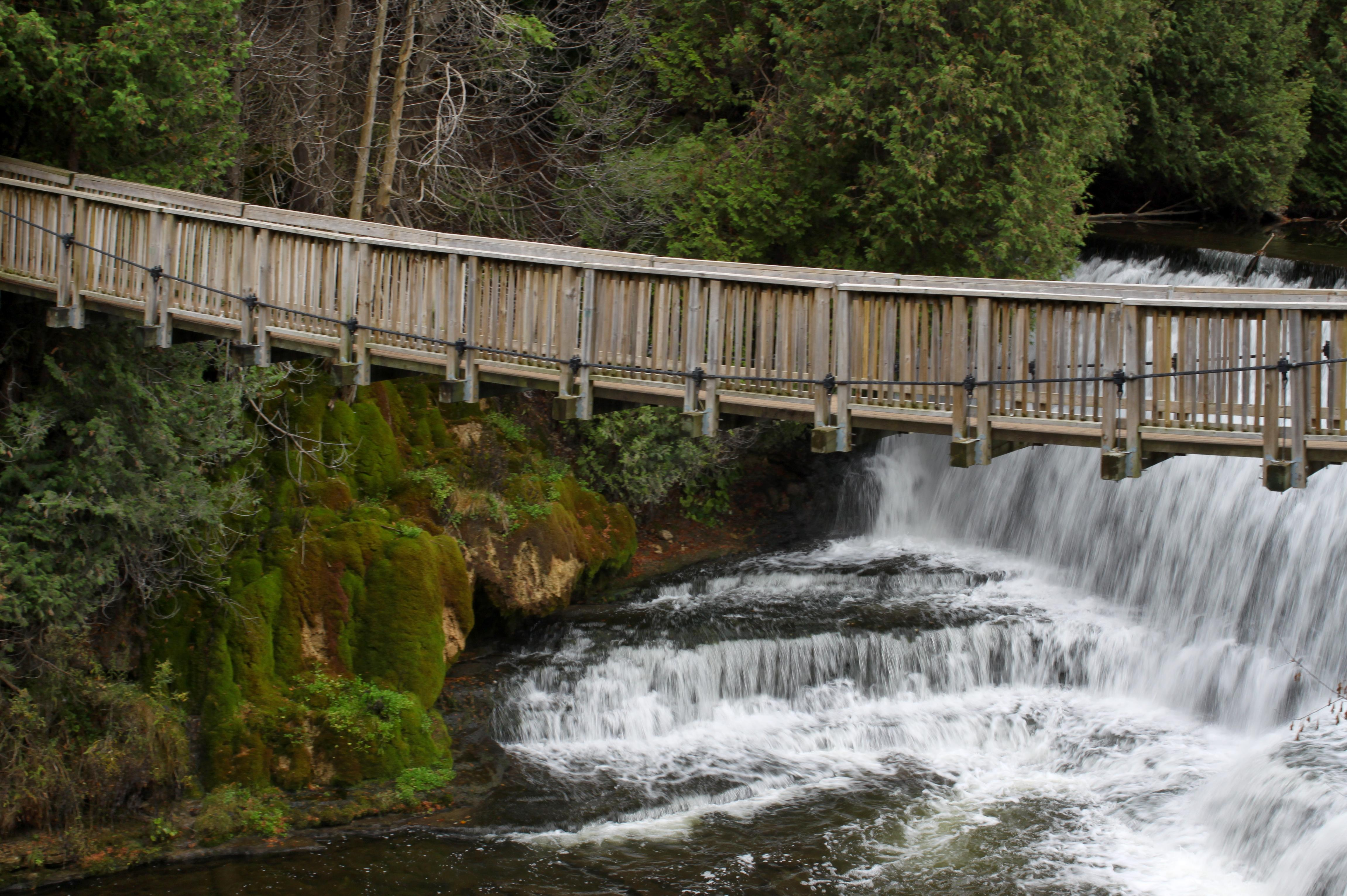 A wooden swing bridge crosses a picturesque river and waterfall